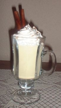 Eggnog topped with whipped cream and cinnamon sticks